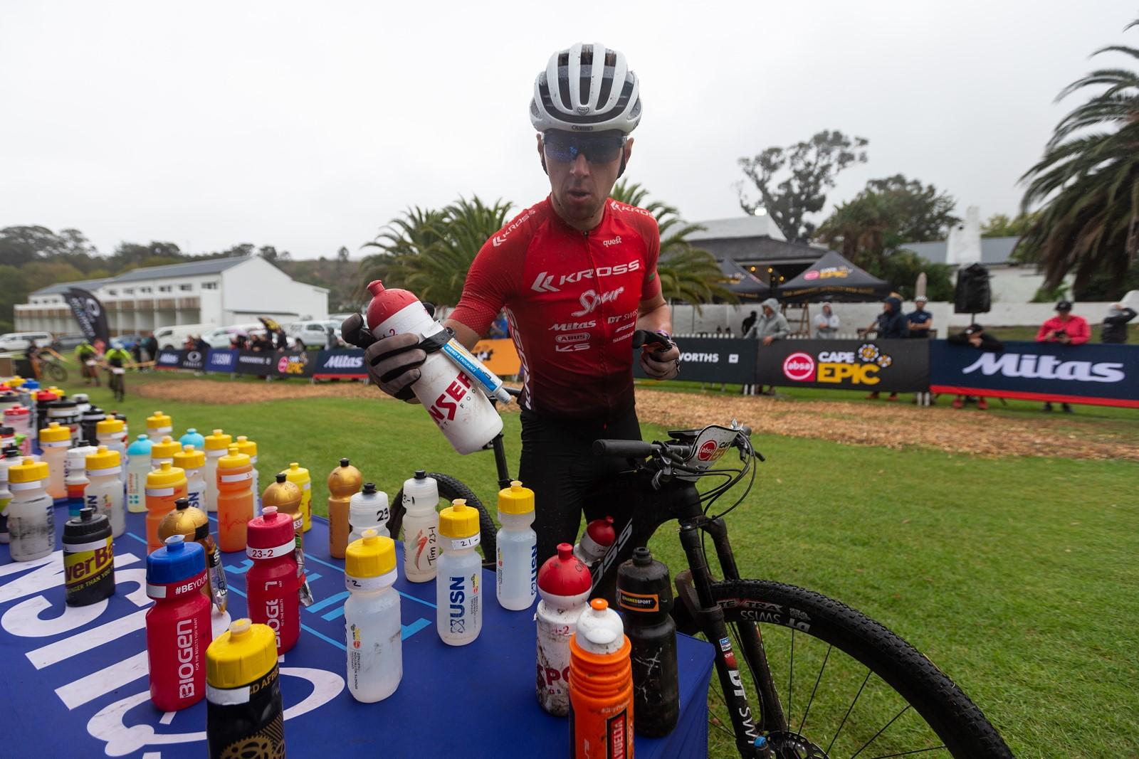 Bidon je nedílnou součástí výbavy každého cyklisty. Ondřej Cink vybírá láhev před etapou na Cape Epic. Foto Michal Červený