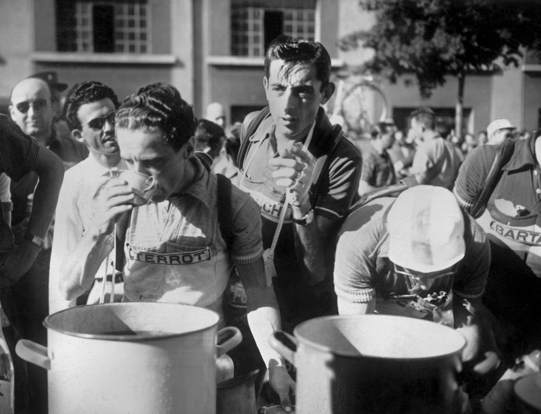 Cyklista Fausto Coppi (uprostřed) se prodírá mezi kolegy pro vodu po desáté etapě Tour de France 1952 s dojezdem v Alpe d´Huez. Foto: profimedia