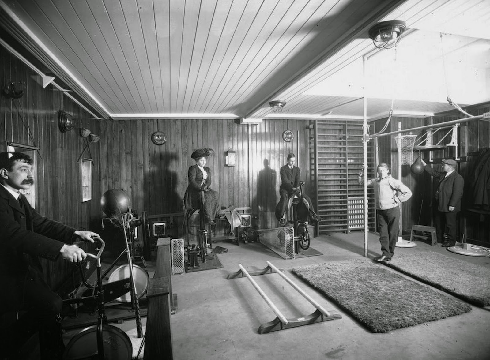 Passangers riding exercise bikes whilst wearing day clothes in a gym on board the Cunard line liner, RMS Franconia (1911).