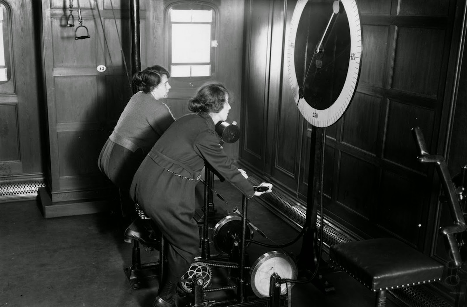 Women using the cycle machine in the gym on board the Homeric Liner (1922).