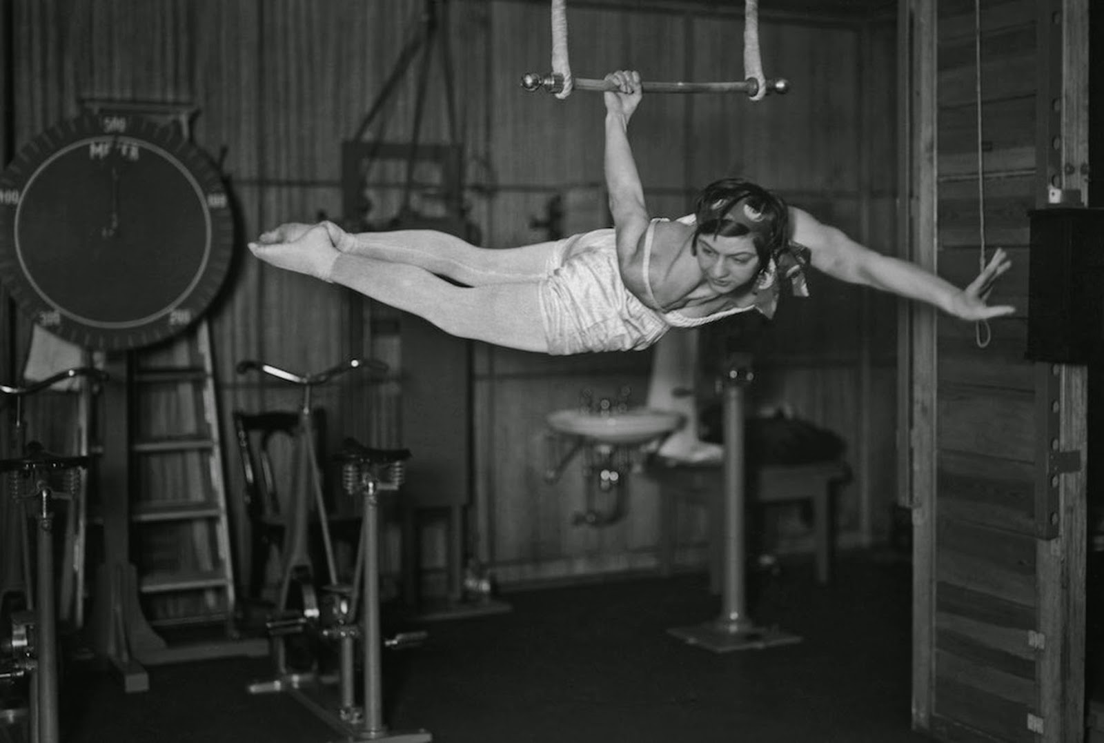 Woman using an apparatus in the gymnasium of the ocean liner S.S. Bremen. A cycling machine in the behind.