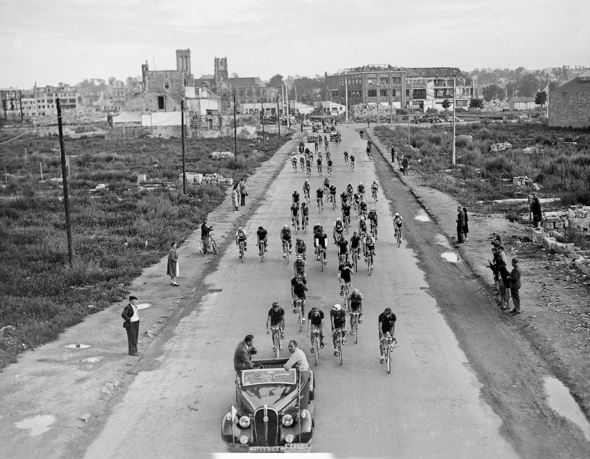 1947:The Tour de France resumed two years after the World War II. In the photo above, you can see the riders leaving the town of Caen. Damage to the buildings is still visible.