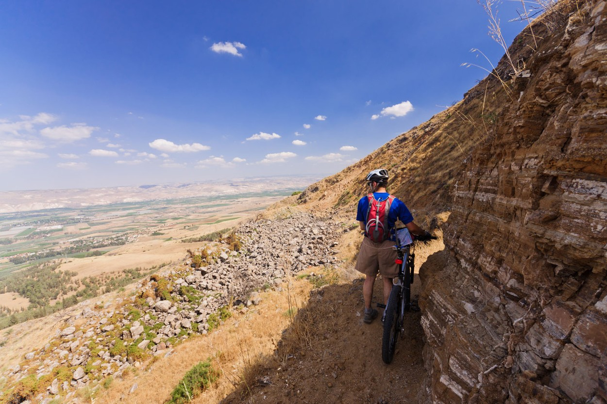 Israel. A cyclist moves his mountain bike through a narrow trail on a mountainside in the Galilee.